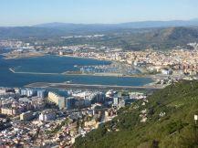 Mittig sieht man die Landebahn von Gibraltar. Oben die Stadt La Linea de la Conception in Spanien. Unten United Kingdom.